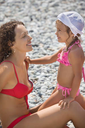 young beautiful woman with pretty little girl in white hat on stony beach photo