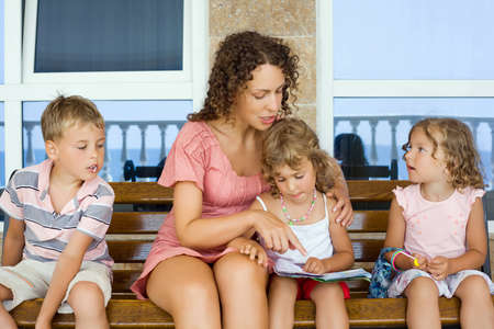mother on bench: young beautiful woman reads book to two little girls and boy on bench  Stock Photo