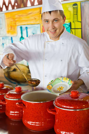 cheerful cook in uniform spoon imposes soup in plate in public catering restaurant, focus on spoon photo
