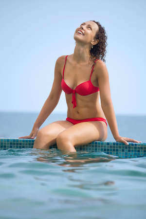 young beautiful sexual woman sitting on ledge pool on resort against sea photo
