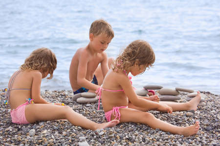 children three together sitting on stony beach, creates pyramid from pebble photo