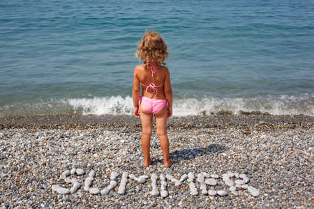are combined: Little girl stands on beach near water. From stones word is combined  Stock Photo