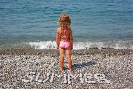 combined: Ni�a se encuentra en la playa cerca del agua. De piedras se combina la palabra