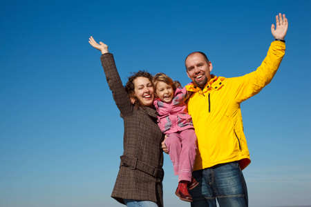 Happy parents together with a daughter with the hands lifted upwards a bright sunny day against the blue sky. photo