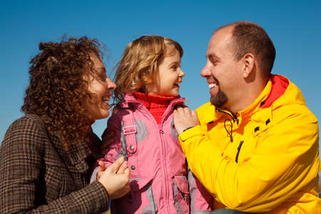 Portrait of happy family against blue sky. Little girl with mum and daddy, in bright autumn day. photo