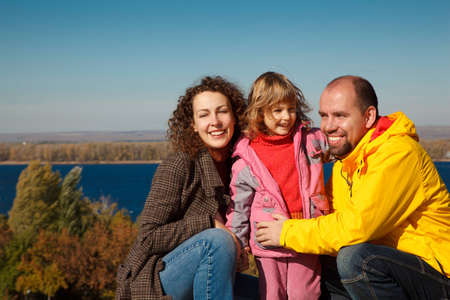 Little girl with mum and daddy, in bright autumn day. Happy family on nature. photo