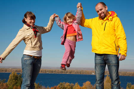 Happy girl shakes on hands at parents against blue sky, in solar autumn day. Everyone looks into camera. photo