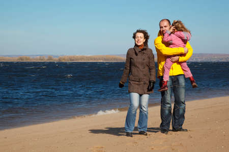 Parents with little girl walk on autumn beach. Productive leisure in open air. photo