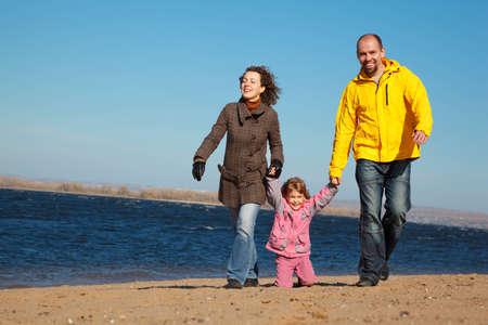 Family of three people walking along beach. Sunny autumn day. photo