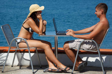 Man and woman sitting at table under open sky on background of sea. Man works for laptop. Girl talking on the phone. photo