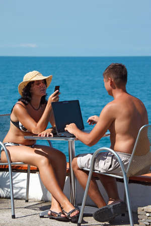 Man and woman sitting at table under open sky on background of sea. Man works for laptop. Vertical format. photo