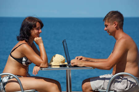 Man and woman sitting at table under open sky on background of sea. Man works for laptop. photo