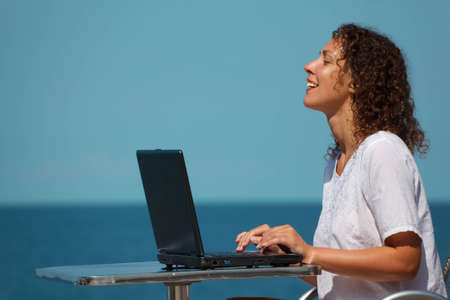 Laughing girl with laptop. Sits at table on beach, warm sunny day. photo
