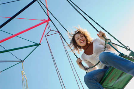 playground ride: Charming girl goes for drive on roundabout. Looking into camera. Stock Photo