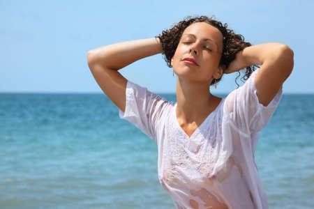 wet clothes: hermosa mujer en ropa mojada en la costa, cerr� los ojos Foto de archivo