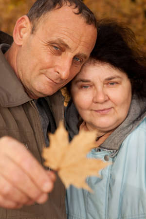 Old man and old woman look at maple leave photo