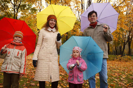 Family from four persons in autumn park with multi-coloured umbrellas. photo