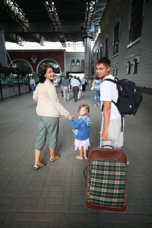 Happy family with little girl at railway station photo
