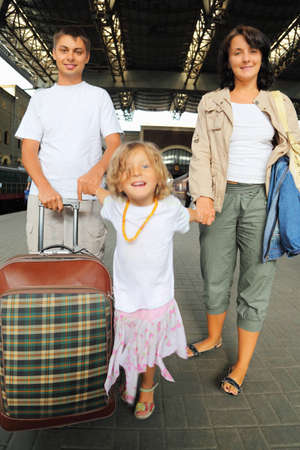 Happy family with little girl at railway station, focus on parents photo