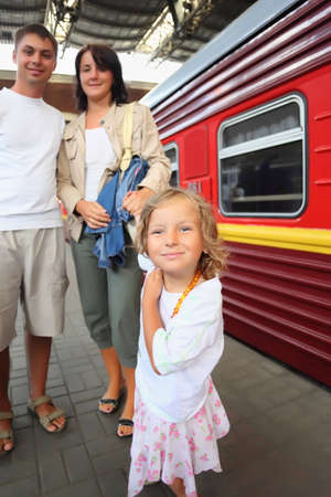 Happy family with little girl at railway station, focus on daughter photo
