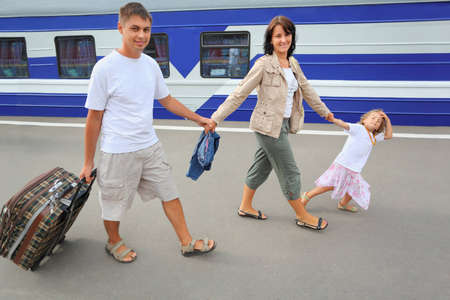 Happy family with little girl going on railway station photo