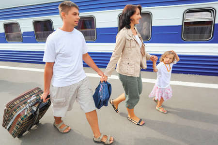 railway station: Happy family with little girl going on railway station Stock Photo