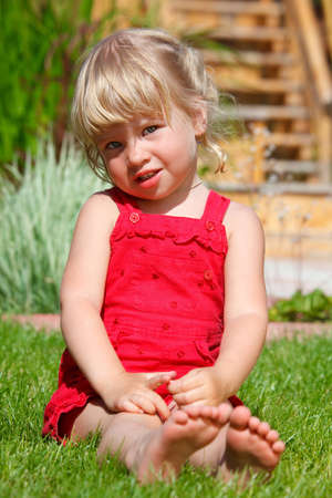 The little girl sits on a lawn photo