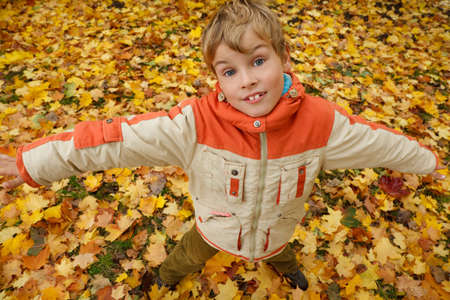 Portrait of boy in autumn park against fallen down leaves. Boy has stretched hands, looks in camera. photo