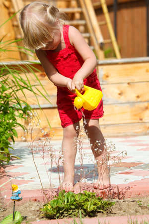 The girl waters flowers from a toy watering can photo