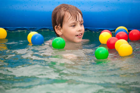 The boy floats in inflatable pool with multi-coloured balls.