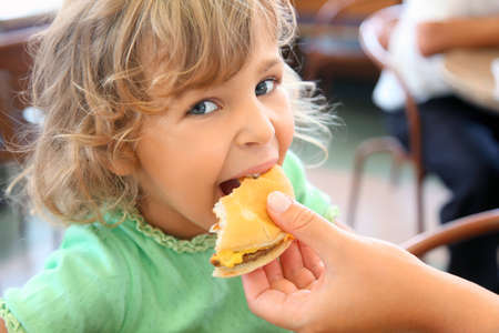 fast meal: pretty little girl eats hamburger from motherss hand