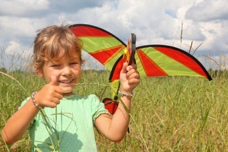 little girl plays kite on meadow with ok gesture Stock Photo - 9110566