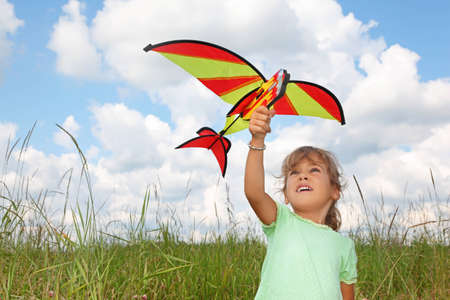 little girl plays kite on meadow photo