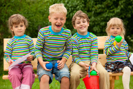 Four children in identical clothes laugh sitting on a bench. photo