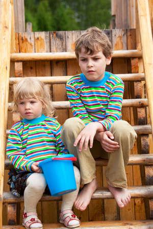 bambini tristi: Fratellino e sorellina su giochi un parco in abiti identici