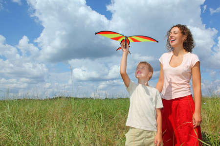 young woman and boy plays kite on meadow photo