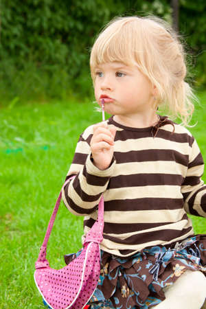 The little girl paints lips in park photo