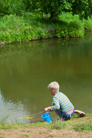 The boy with a net on the bank of lake photo