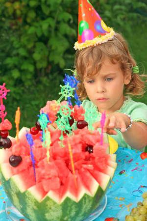 little girl in cap eats fruit in garden, happy birthday photo
