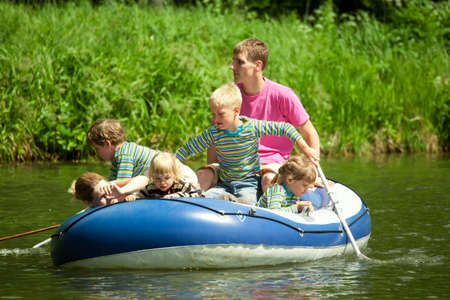 children pond: Children go for a drive on an inflatable boat under supervision of adults