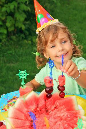 little girl  in cap eats fruit in garden,happy birthday photo