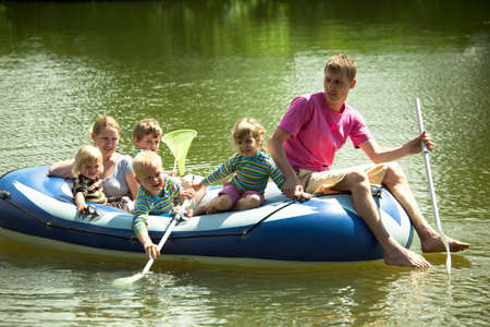 Children and adults float on an inflatable boat and fish a net. photo