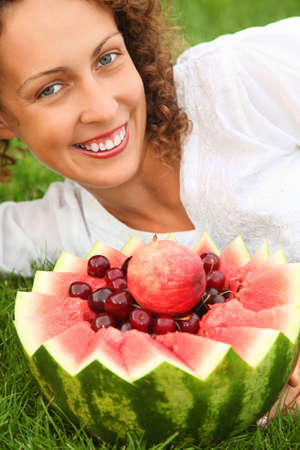 young beautiful woman with fruit lying on alawn photo