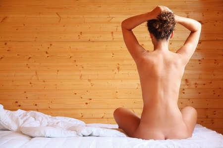 mujer desnuda de espalda: hermosa caliente mujer desnuda sentada en la cama en la sala de madera acogedor, sentado en la parte posterior