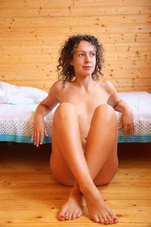naked beautiful hot woman woman sitting on floor near bed in cosy wooden room    photo