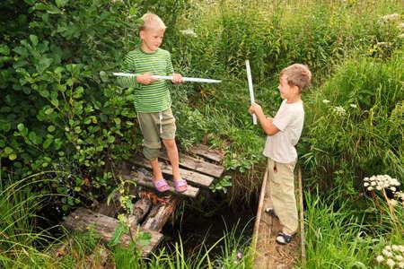 battling: Two boys with sticks battling for fun on bridges over stream  Stock Photo