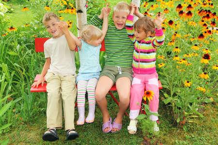 Children sitting on bench in garden, having joined hands photo
