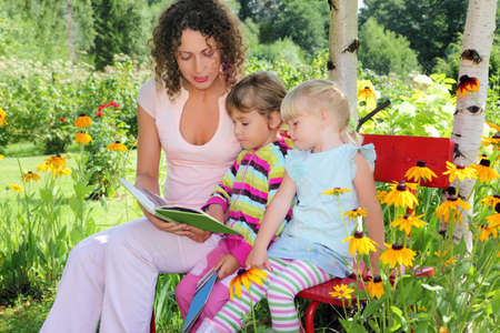 young woman reads the book to two little girls in garden photo