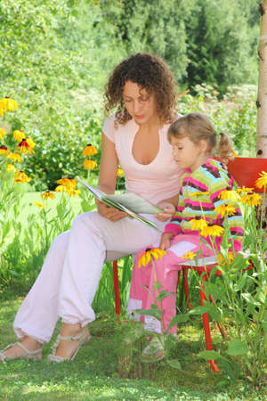 young woman reads the book to little girl in garden Stock Photo - 9110587