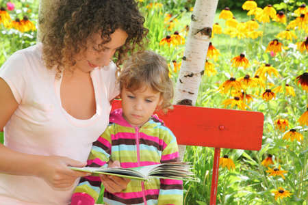 young woman reads the book to little girl in garden Stock Photo - 9110582